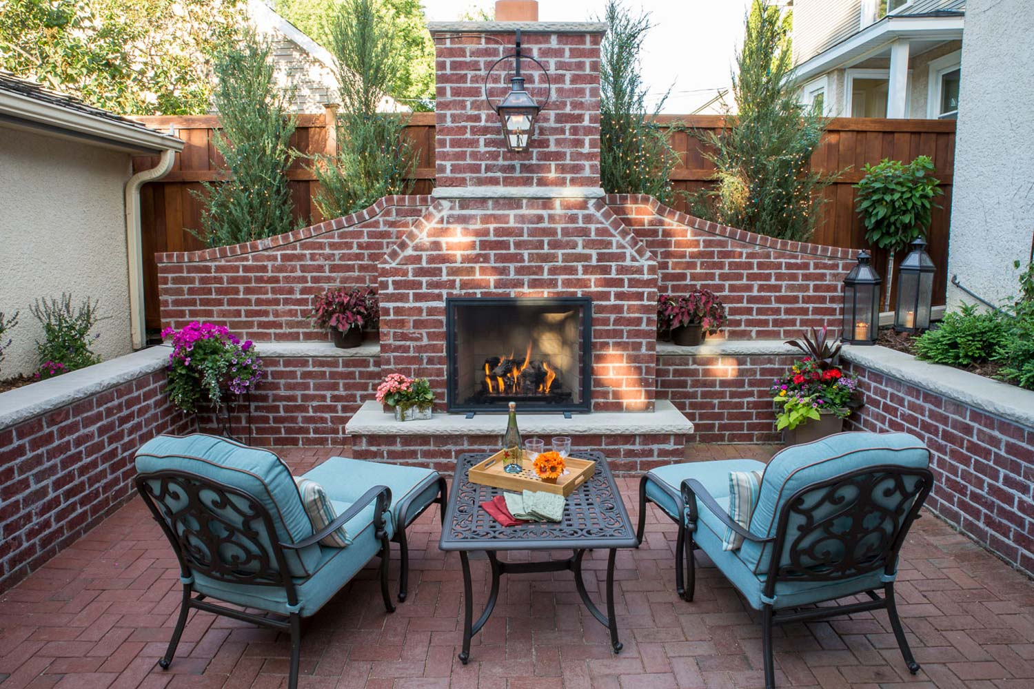 Centered on a hand-build re brick fireplace and two aqua blue outdoor chez lounge chairs