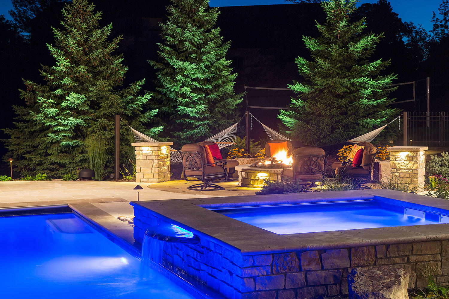 backyard hot tub and swimming pool with dramatic blue lighting