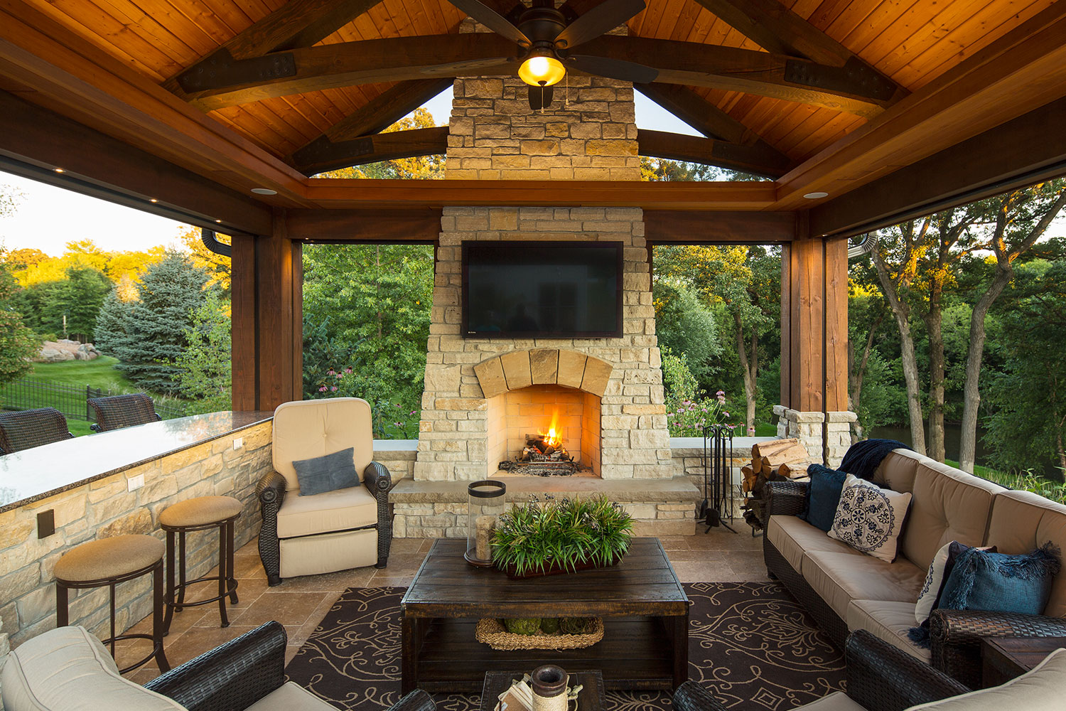 Outdoor Living Room with Stone Fireplace and Travertine Floor