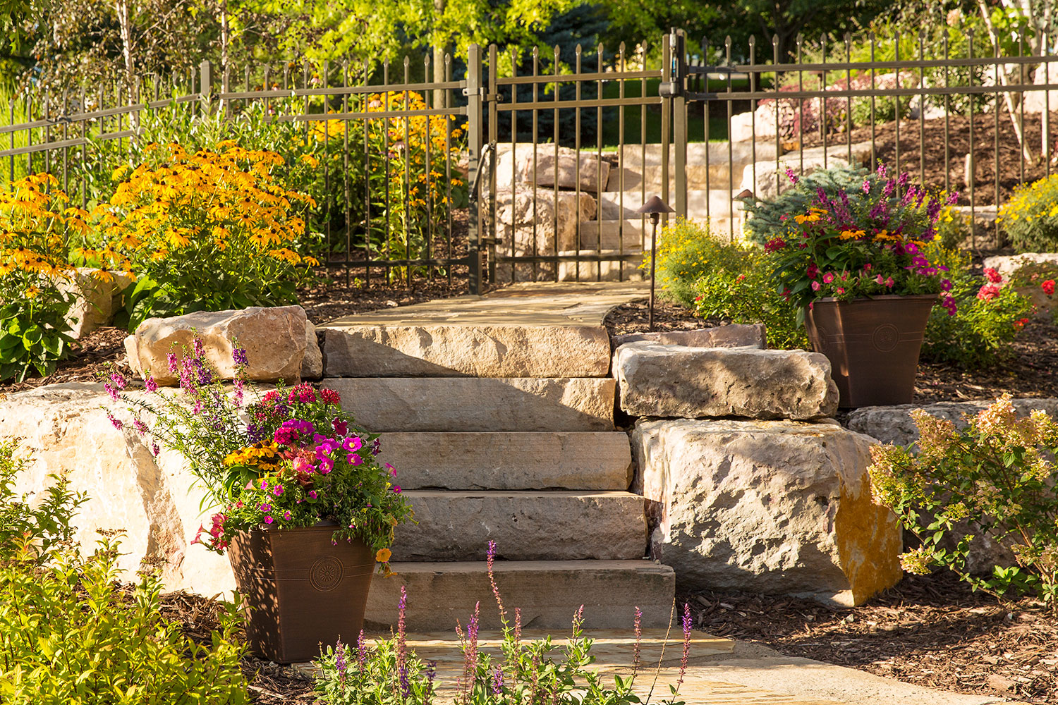Stone steps and walkways provide safe, easy access to the backyard swimming pool