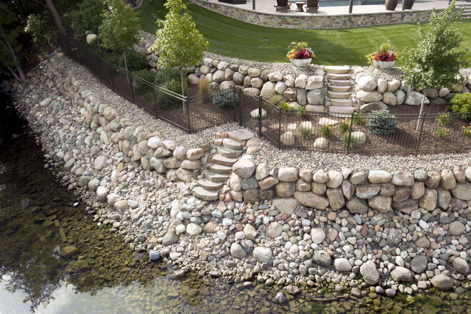 Tiered boulder wall created with tons of rock, black fence and plantings
