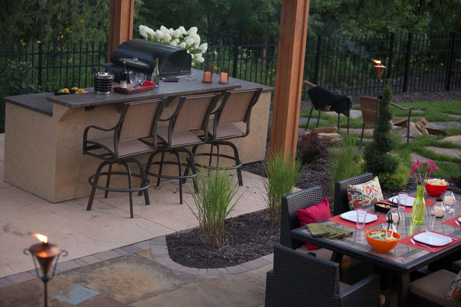 dining patio separated from outdoor pergola bar by tall grass plantings