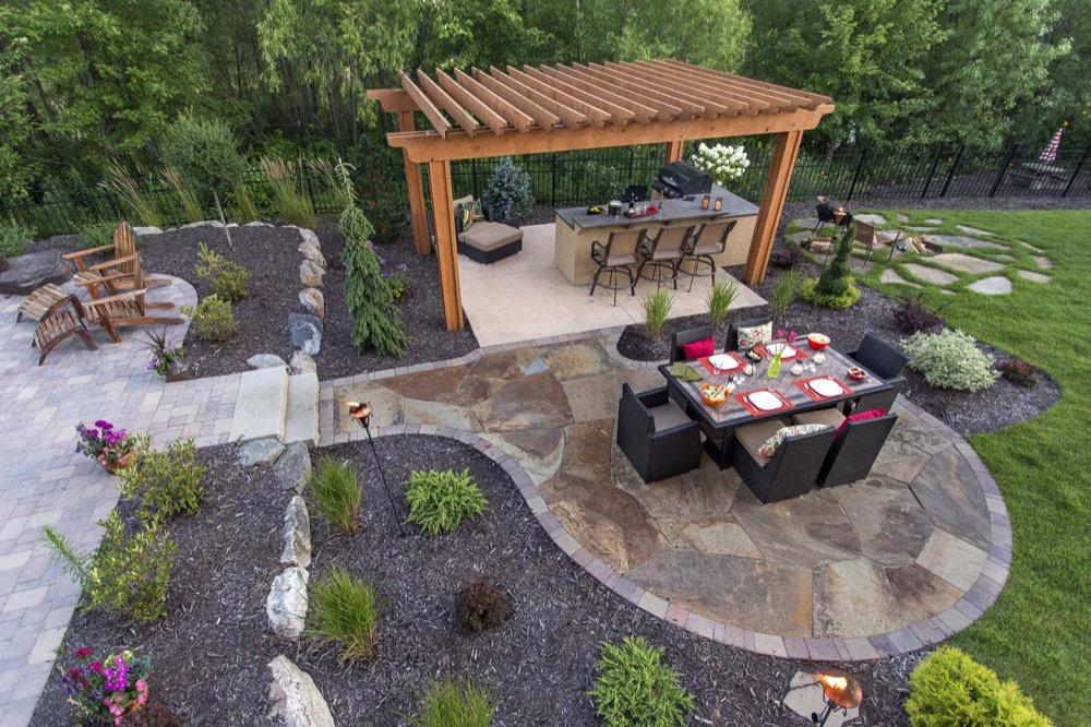 Outdoor chilton stone dining patio next to an outdoor bar under a pergola - Minneapolis Metro Area