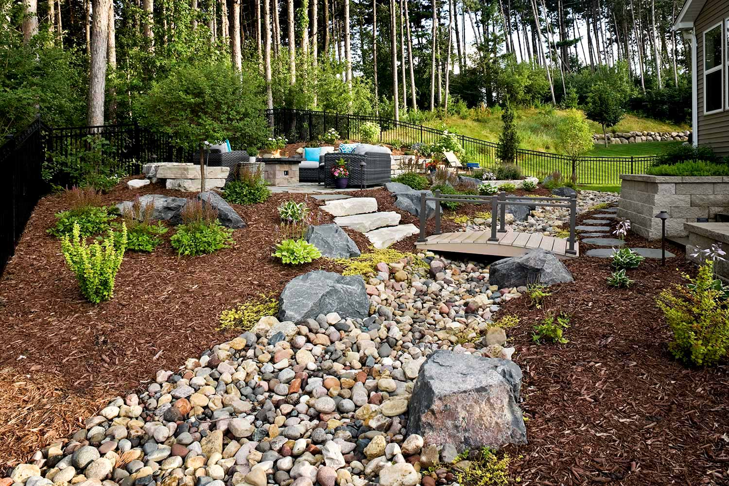 backyard without grass has a dry creek bed to help manage landscape drainage