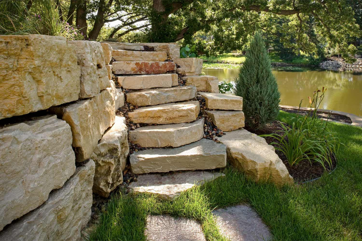 Stacked boulder retaining wall with stone staircase.