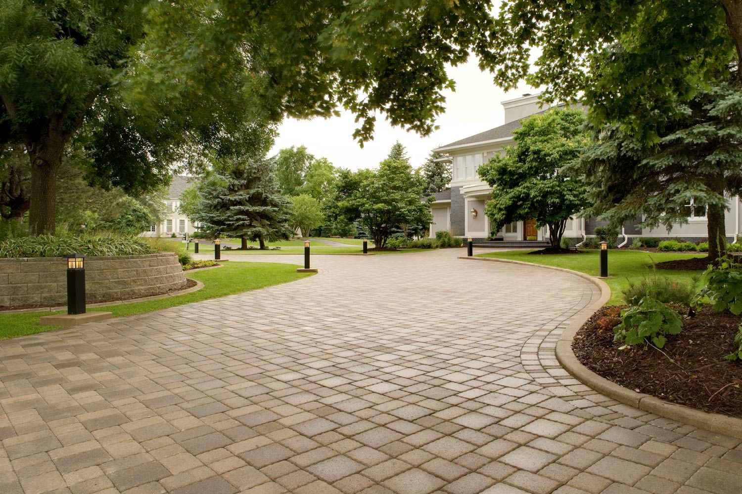 Long and elegant paver driveway.