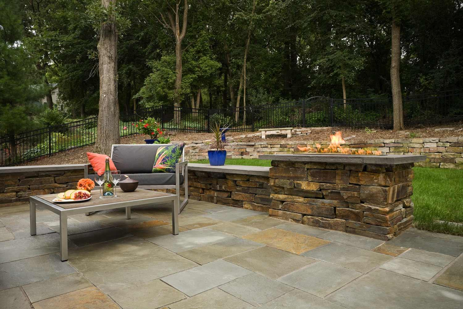 Stacked stone seat wall and natural gas fireplace